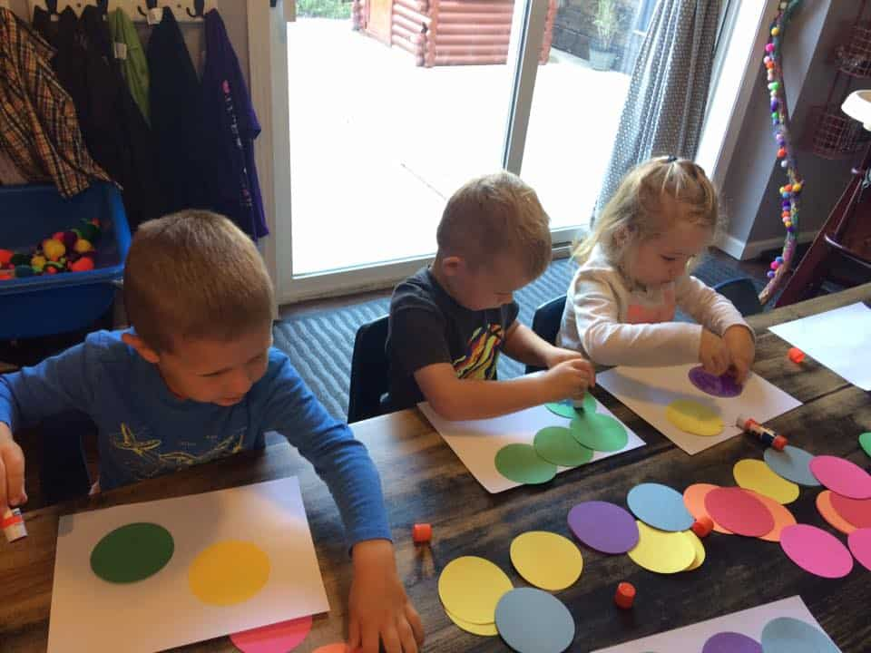 three young children gluing circles on paper during a gluing activity for preschoolers