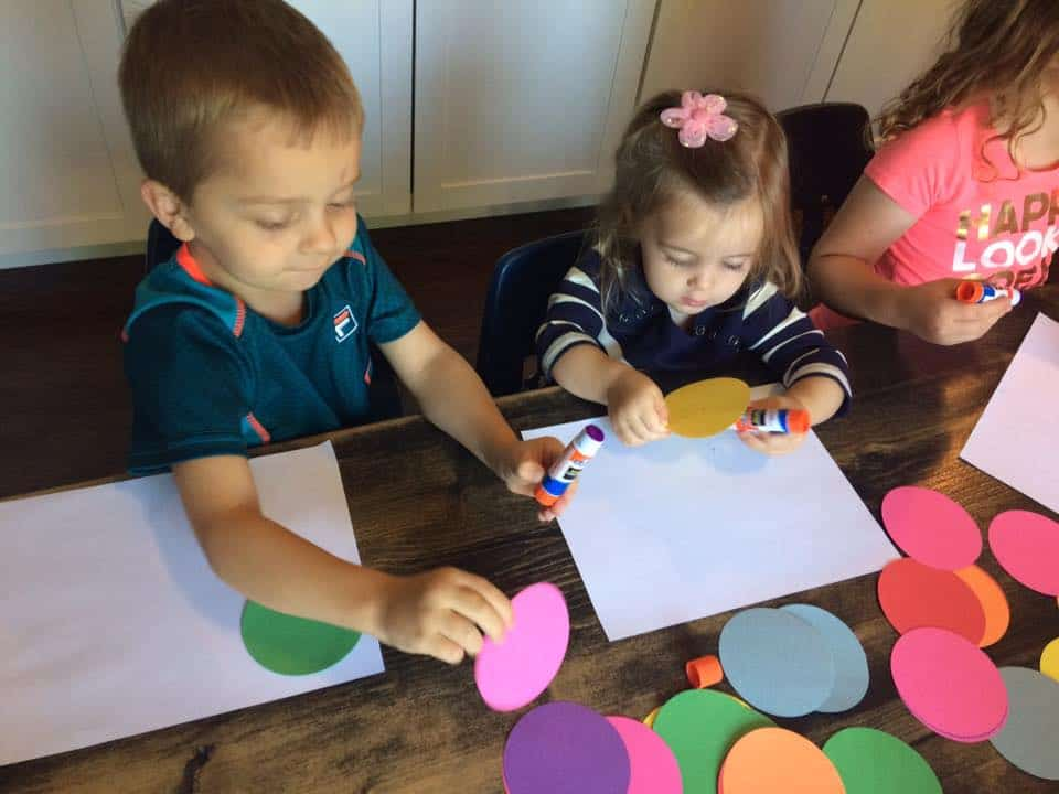 preschool kids gluing circles onto large piece of paper