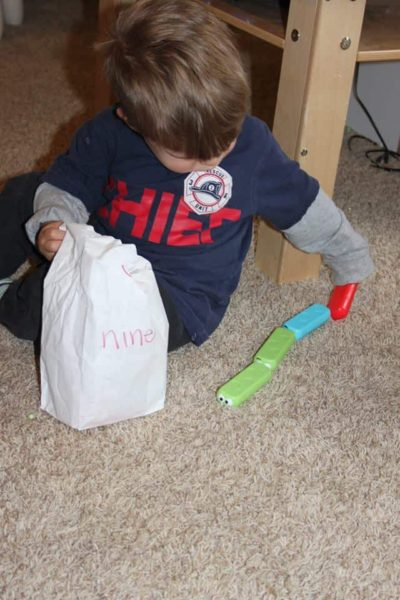 hands on math activities for preschoolers with a young boy counting blocks
