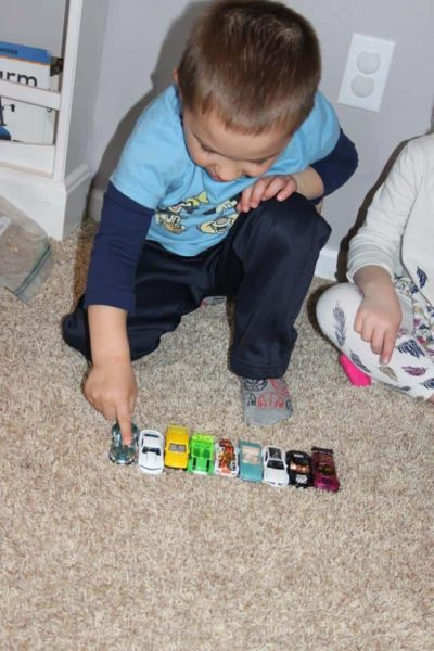 young boy counting toy cars during hands on math activities for preschoolers