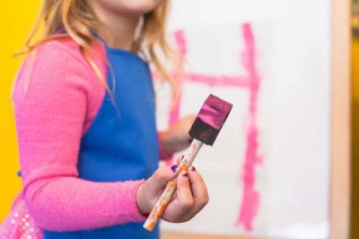 young girl wearing blue apron holding a paint brush