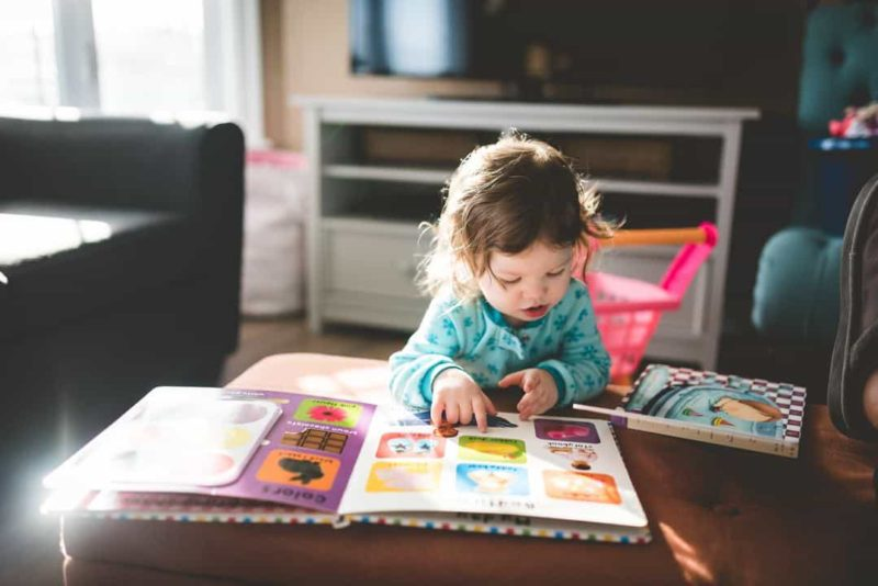 young toddler girl with fever reading a book