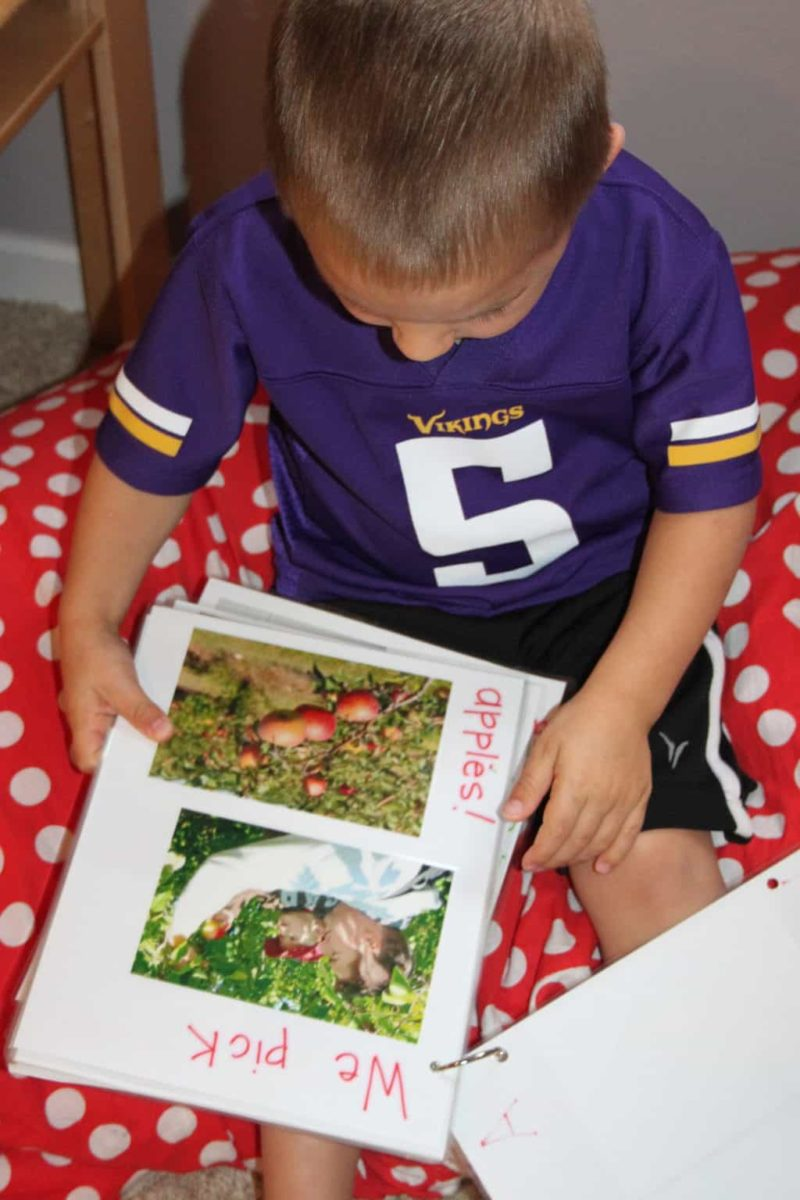 little boy wearing football jersey reading book about apples