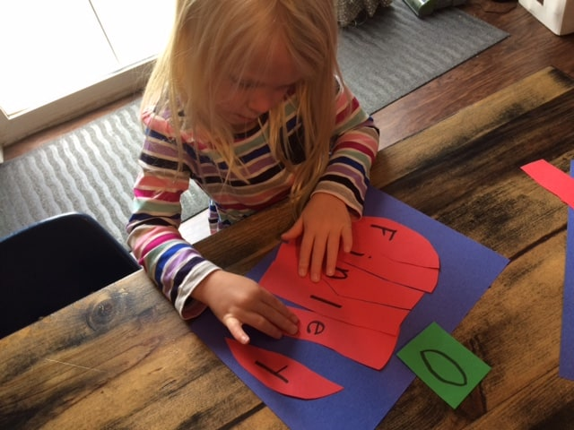 preschool girl gluing letters together to make a paper apple