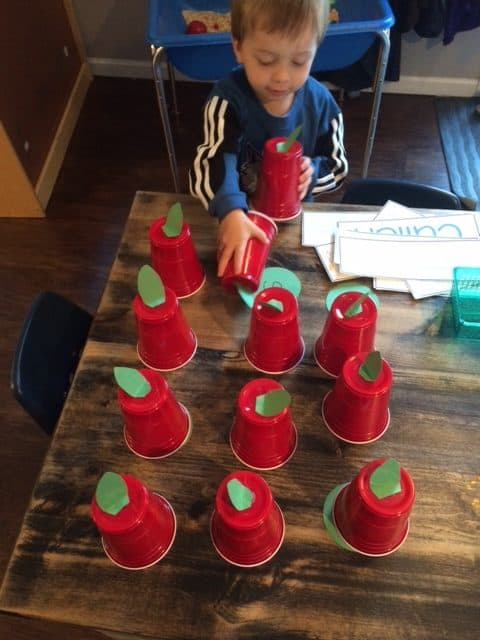 little boy playing with solo cups that look like apples