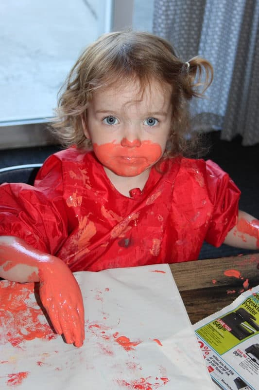 toddler girl covered in peach paint on hands and face