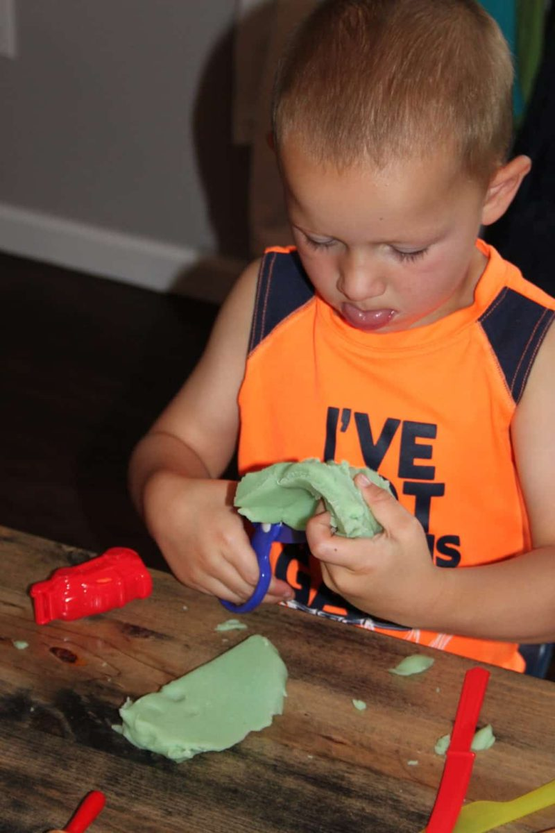 young boy cutting playdoh with scissors and sticking out tongue