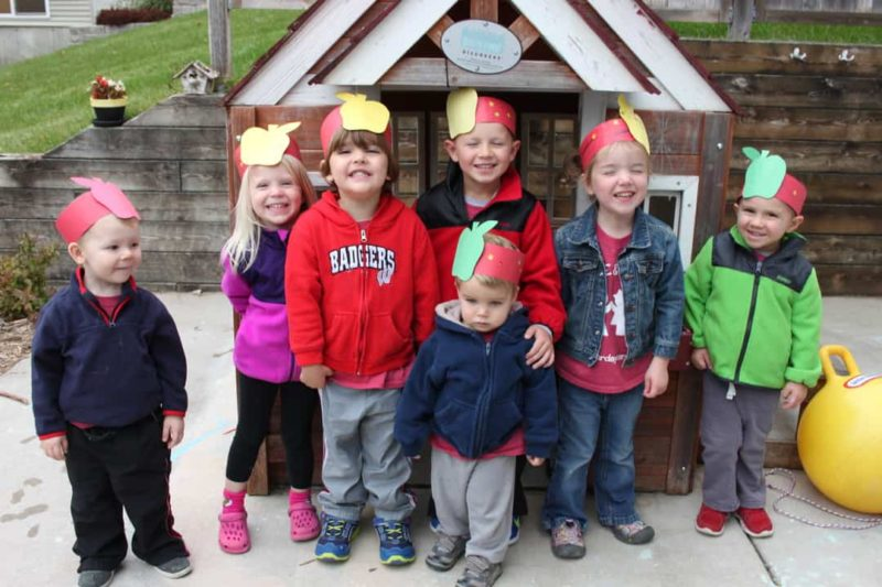 group of young kids outside wearing paper apple headbands