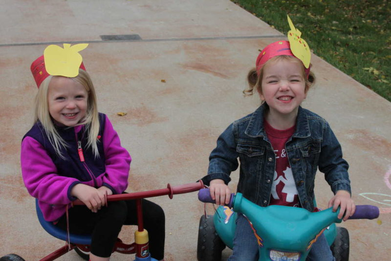 two little girls smiling on riding toys wearing paper apple headbands