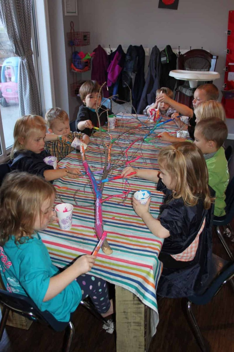 group of preschool kids at art table painting stick for easy art activitiy