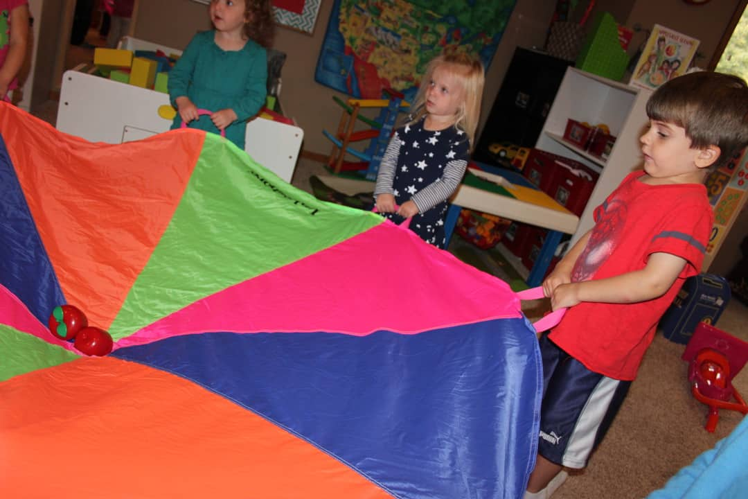 young kids holding a colorful parachute with plastic apples in the center