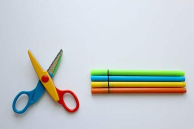 kid scissors lying open next to 4 colorful markers