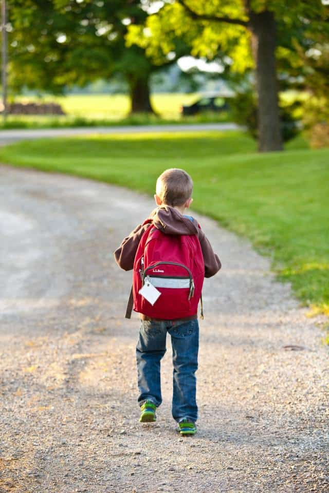 young boy walking down gravel path with a red backpack on his back