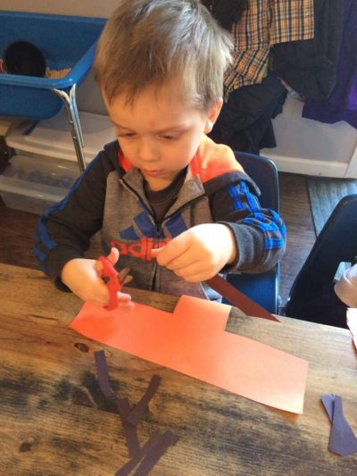 young boy cutting a piece of orange paper at the art table