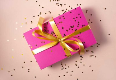 gift wrapped box with pink paper and gold bow