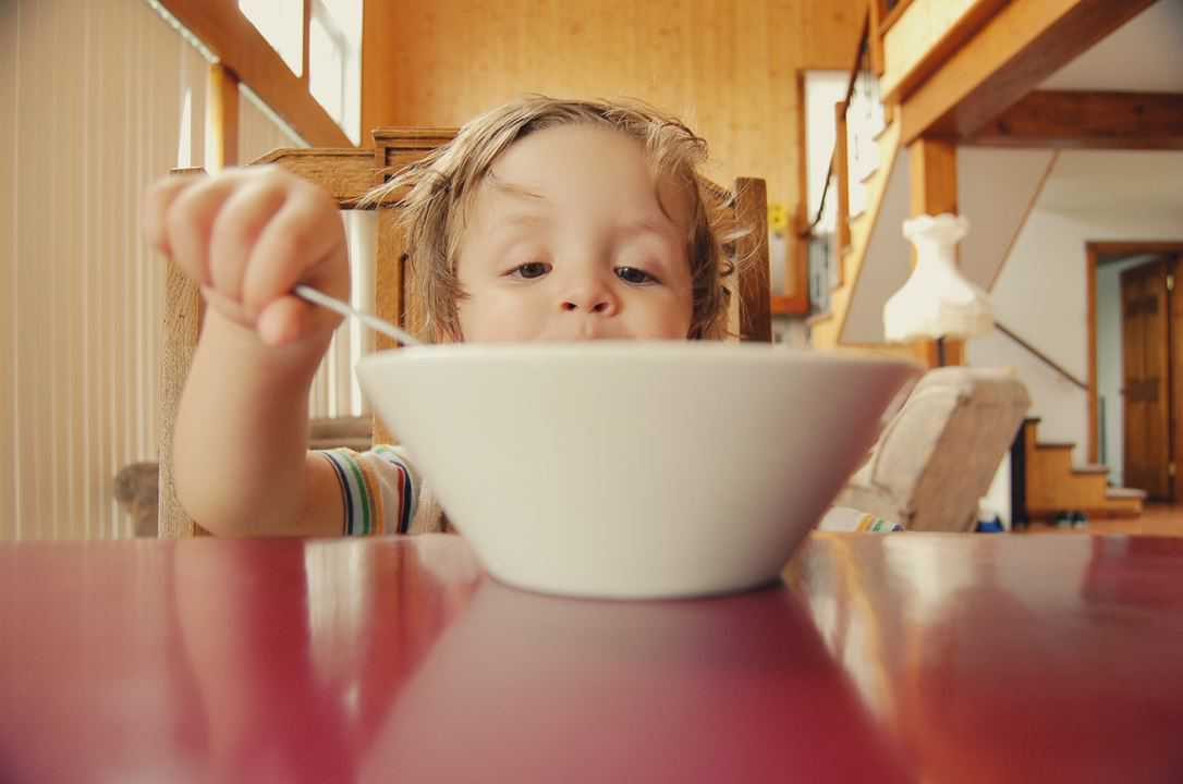boy eating out of a bowl with meal from lunch menu ideas