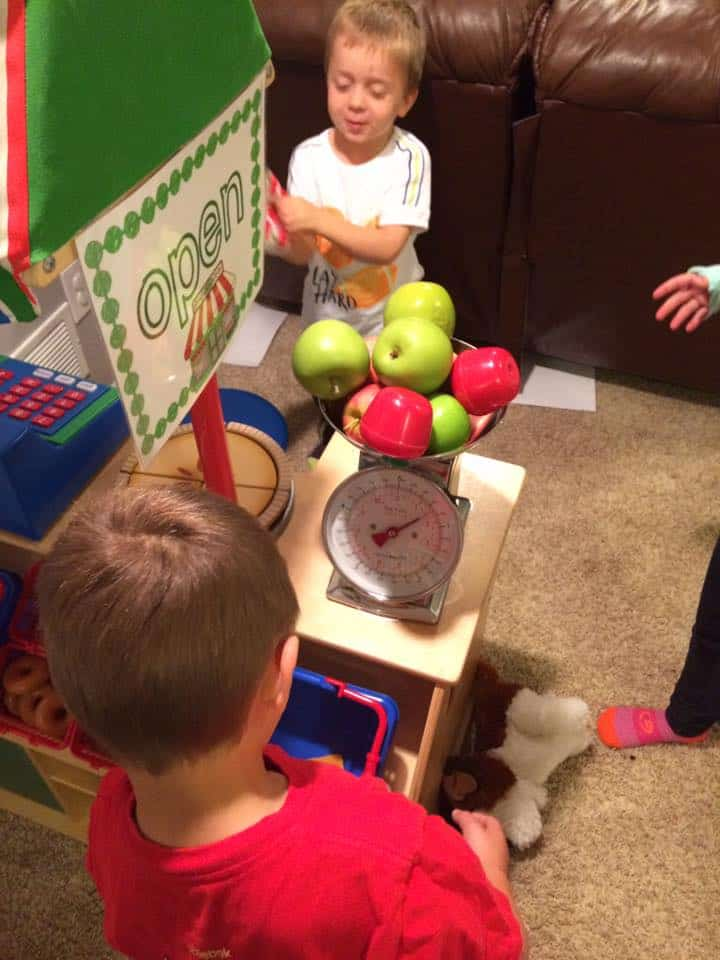 preschool boys organizing apple stand