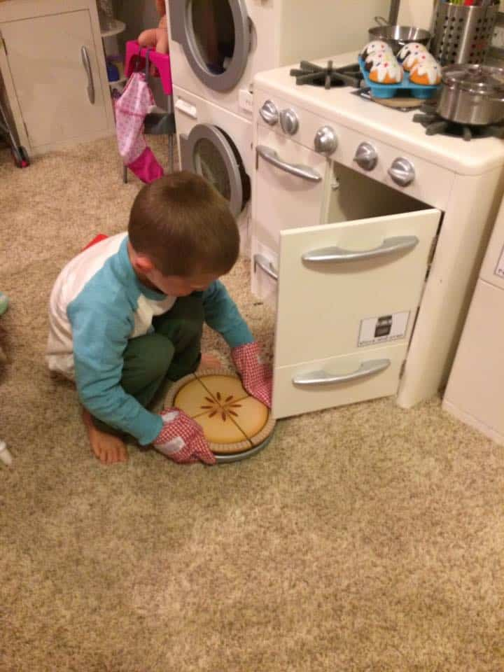 young boy taking a pretend apple pie out of toy oven