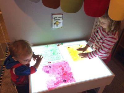 preschooler and toddler standing at light table with apple activity