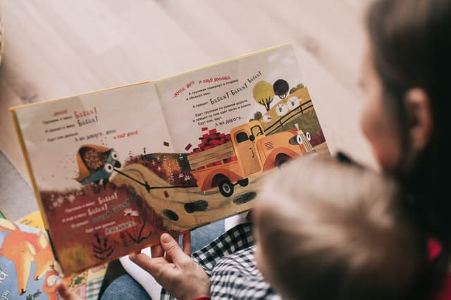 boy reading book with daycare provider