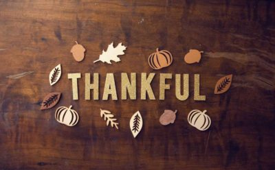the word thankful on a table with leaf cut outs