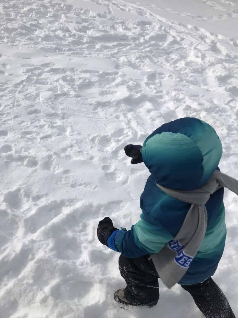 young boy wearing winter gear in family child care walking in snow